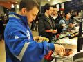 A boy in a blue jacket serves himself from a warming dish in the buffet line along with other students.