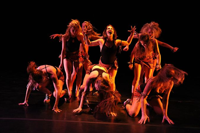 Nine girls with crazy hair stand on a dark, dimly lit stage, three crouched in front and four standing in back.