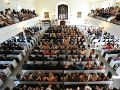 Aerial shot of rows of pews with students sitting, man lecturing at the front.