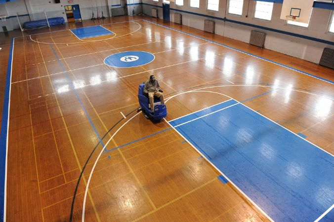 Dark wooden gym floor with blue accents is being polished.