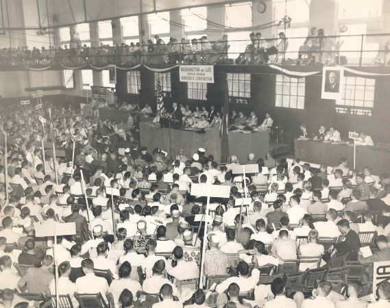Black and white photograph of a gym filled with people sitting in chairs holding up signs, in front of the chairs of Mock Convention.