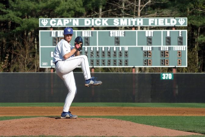 A Washington and Lee baseball player winds up to pitch on the dirt mound with a faded green scoreboard in the background, which reads