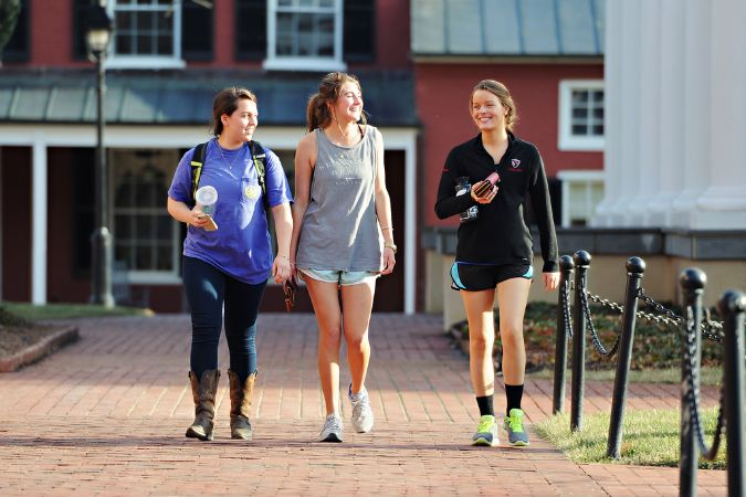 Three girls in athletic clothing walking on a brick walkway in front of a red building.
