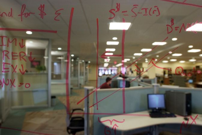 Equations are drawn in red marker on glass, with library computers behind it.