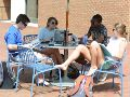 Four students sit on blue chairs outside at a round metal table, looking at books and laughing, against the brick background of the library.