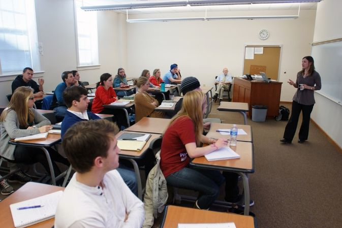Students sit at two-person desks in front of a whiteboard and speaker, with a desk in the left of the classroom.