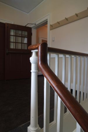 Staircase with wooden banister and white slats.