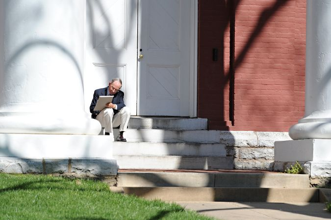 A professor sits on the steps of Newcomb, dwarfed by the large door behind him and large white pillars flanking him.