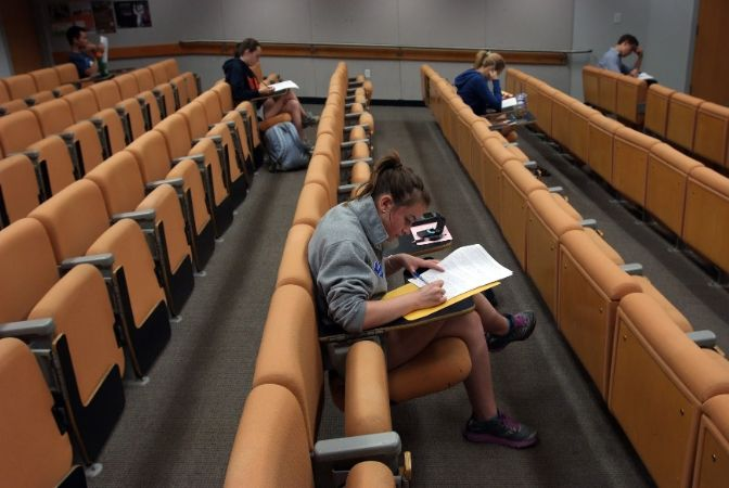 There are seven long, staggered rows of orange chairs with flip out desks--students are scattered throughout, taking exams.