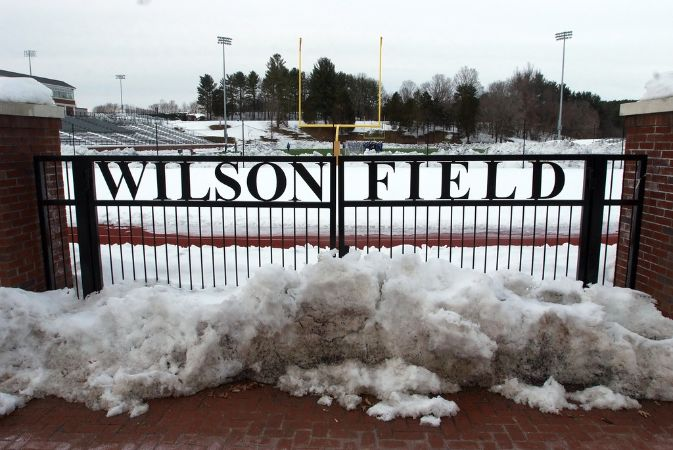 Metal sign/gate reading Wilson Field; field covered in snow