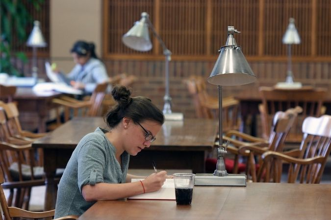 Student studying at wooden table with metal lamp.