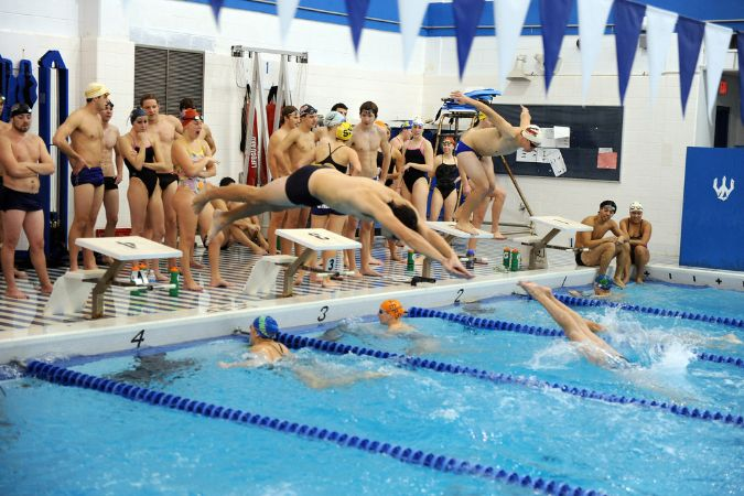 A cluster of swimmers watch as their teammates jump into the water in a relay.