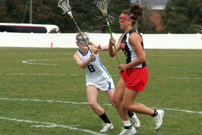 A W&L lacrosse player in white runs and holds her stick high against an opposing player.