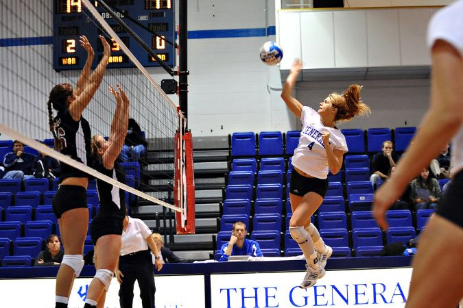 A W&L player is jumping in the air, about to hit the volleyball over the net.