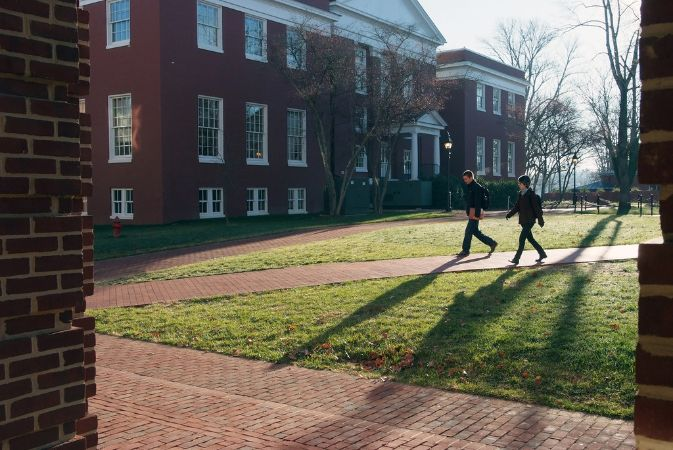 Two students walk down a brick walkway to class-Huntley Hall, a three story red brick building with many white windows and a small portico.