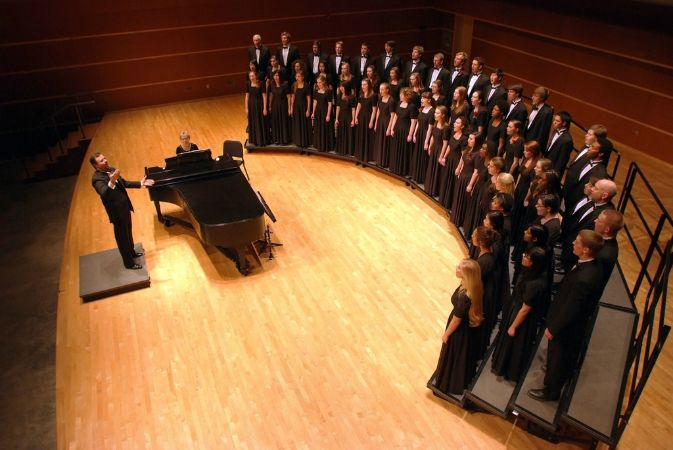 The choral director conducts from a light wooden stage next to a piano, across from men and women singers on rounded risers.