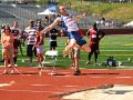 A track team member is mid-long jump above a sand pit.