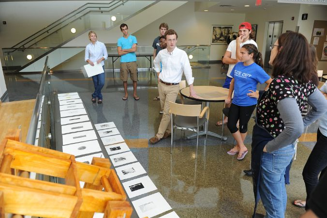 Six students and a professor look at prints on a shiny grey floor, in the Wilson Atrium which is a very open space.